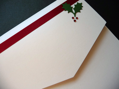 Ivory portrait pocketfold with red ribbon and a holly theme with diamantes
