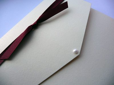 Ivory portrait pocketfold with knotted burgundy ribbon