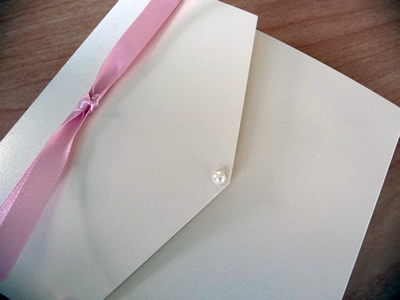 White portrait pocketfold with pale pink knotted ribbon and a pearl