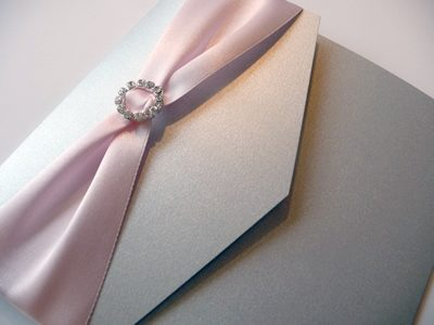 Silver portrait pocketfold with a pale pink colour scheme and round diamante ribbon buckle
