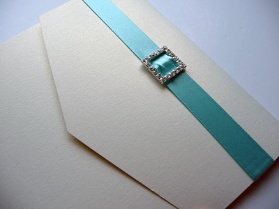 Ivory portrait pocketfold with a turquoise colour scheme and square diamante ribbon buckle