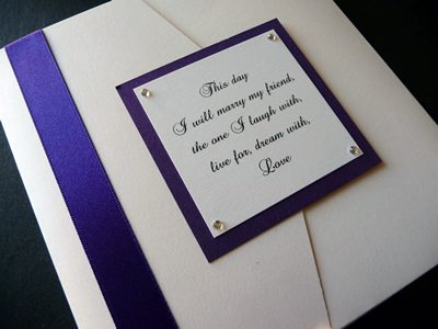 White landscape pocketfold wedding invitation with a purple colour scheme and verse on the plaque