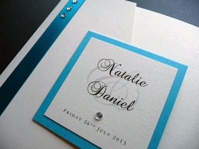 Ivory landscape pocketfold wedding invitation with a turquoise colour scheme and plaque detail