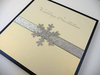 Navy pocketcard wedding invitation with silver glitter ribbon and a large glitter snowflake