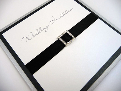 Silver pocketcard wedding invitation with a black colour scheme with a square diamante buckle