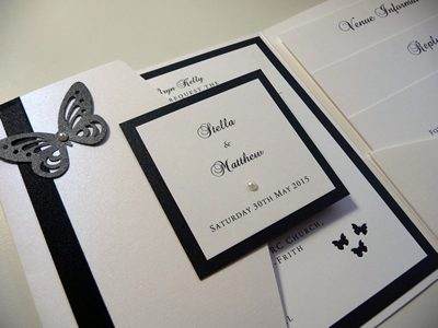 White landscape pocketfold wedding invitation with a black colour scheme, butterfly theme and personalised plaque