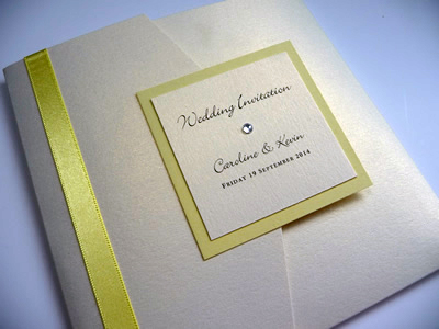 Ivory landscape pocketfold wedding invitation with a yellow colour scheme and personalised plaque