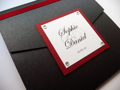 Black portrait pocketfold wedding invitation with a red colour scheme and personalised plaque