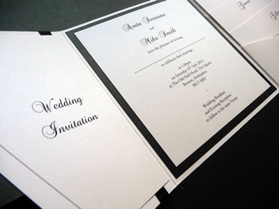 White landscape pocketfold wedding invitation with a black colour scheme and personalised plaque