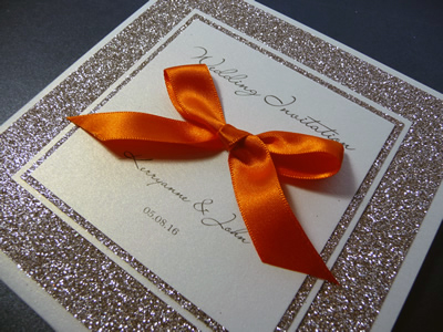 Ivory and champagne gold glitter pocketcard wedding invitation with a plaque detail and bright orange ribbon bow