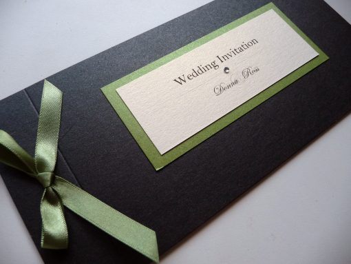 Sage green and black cheque book with a bow and plaque detail