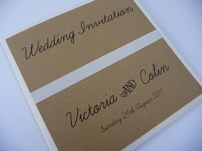 Rustic themed folded wedding invitation with flat ribbon on the cover