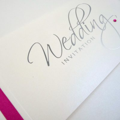 Silver and white foiled script wedding invitation with fuchsia pink flat ribbon