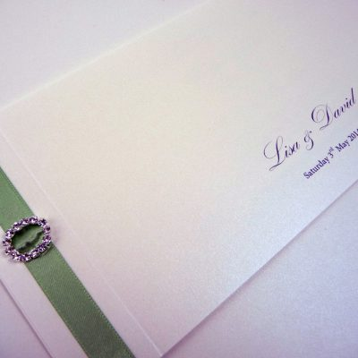 Ivory and sage green cheque book style wedding invitation with an oval ribbon buckle