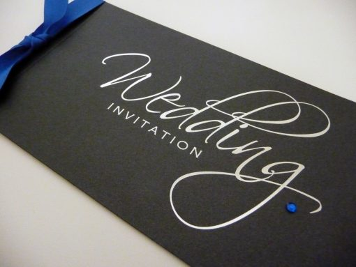 Silver and Black foiled script cheque book wedding invitation with royal blue ribbon and diamante