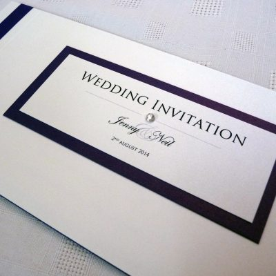 Navy and ivory cheque book invitation with a double mounted plaque and flat ribbon
