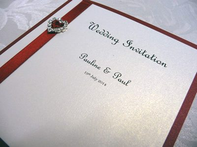 Red and ivory folded wedding invitation with a heart shaped ribbon buckle