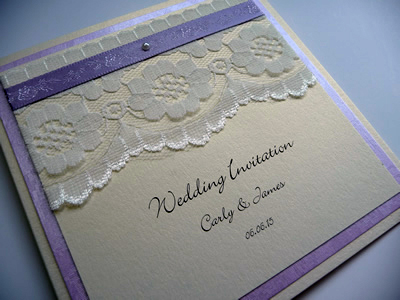 Ivory & Lilac folded wedding invitation with lace above the wording