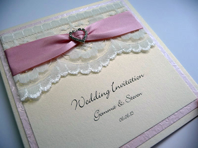 Vintage ivory & pink folded invitation with lace and a fancy heart shaped diamante ribbon buckle
