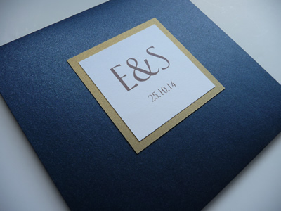 Navy folded invitation with a double mounted white and gold plaque detail