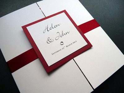 Red and Ivory gatefold wedding invitation with a plaque and red satin ribbon belly band