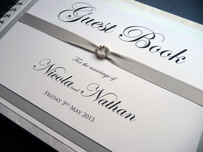 Silver and White Wedding Guest Book and a round shaped ribbon buckle
