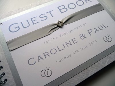 Silver and White Wedding Guest Book with a ring theme and diamond shaped ribbon buckle