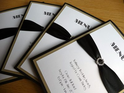 Black and gold themed event menus with a round diamante buckle