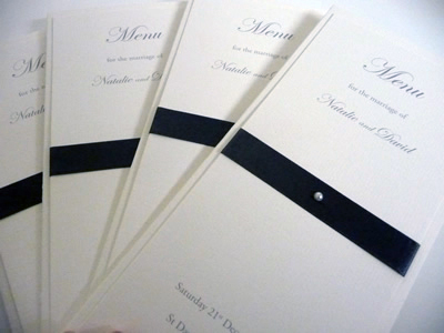 Ivory and black folded menu card with flat ribbon with a folded paper insert