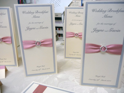 Silver and dusky pink triple mounted folded menus with a round diamante buckle