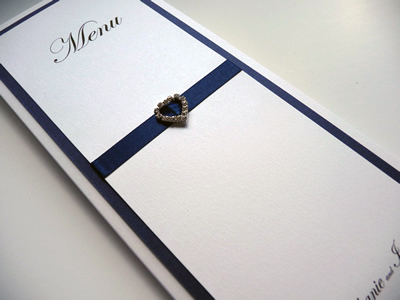 Ivory and navy triple mounted folded menus with a heart shaped diamante buckle