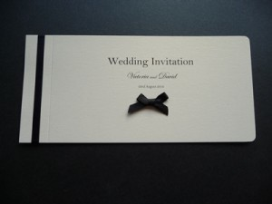 Black and Ivory cheque book wedding invitation with a small bow on the cover