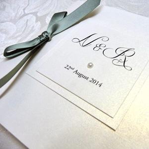 folded invitation with sage green ribbon