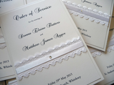White Order of Service booklets with white lace and satin ribbon