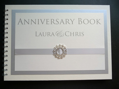 Wedding Anniversary Guest Book with a white and silver colour scheme with fancy ribbon buckle
