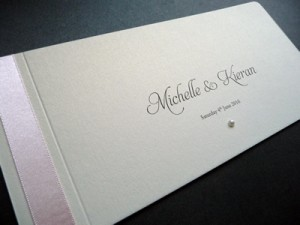 Pale pink and ivory cheque book wedding invitation with a round ivory pearl