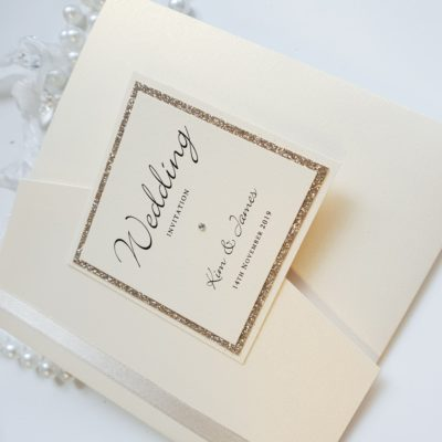 Ivory and Gold Glitter themed Pocketfold wedding invitations with ivory ribbon