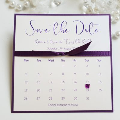 Purple and White Save the Date with Calendar style wording and a diamante heart