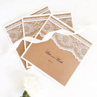 Rustic folded wedding invitations with lace and ribbon detail